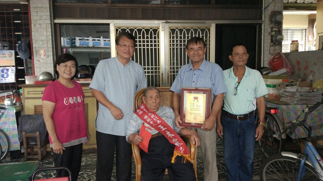 在屏東竹田鄉竹田村擔任33年村長的王木霖(中)獲得今年全國模範老人的表揚。記者林...