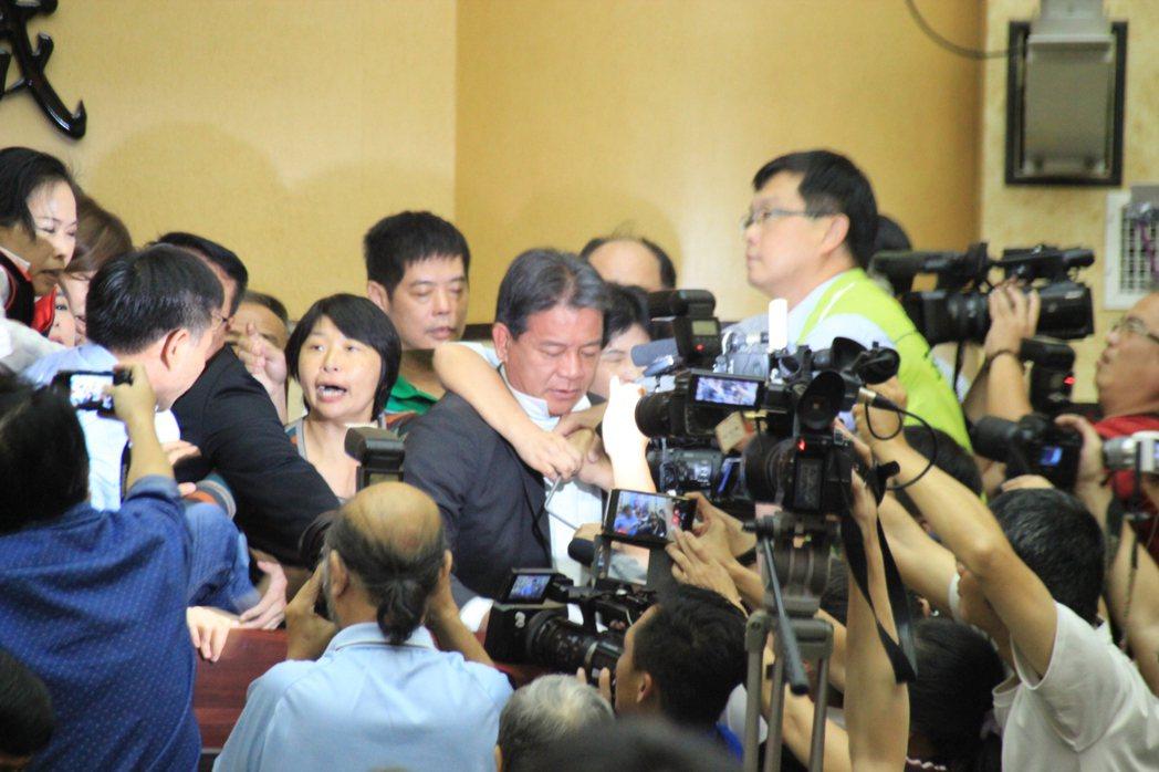 台南市議會今天召開臨時會,藍、綠黨團在主席台爆發激烈衝突,被夾在中間的代理議長郭...