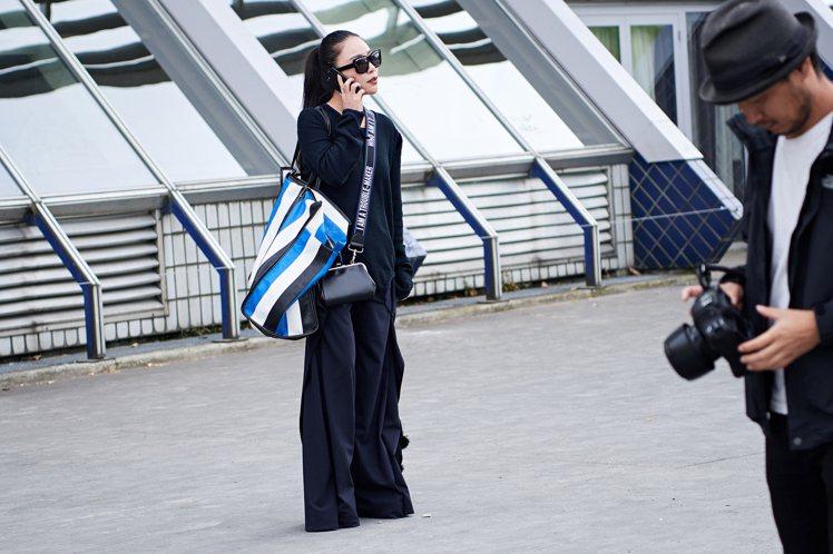 時裝周達人用休閒寬鬆的深色套裝搭配BALENCIAGA藍色款「BAZAR」包。圖...