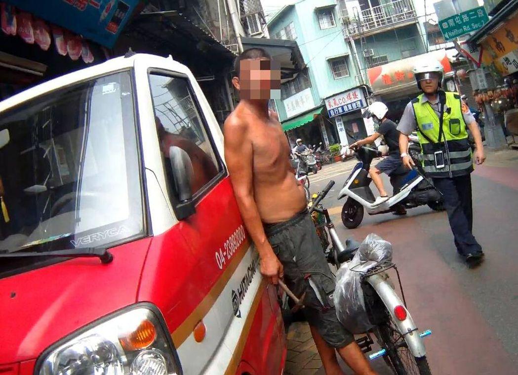 王姓無業男子(左)從單車的車籃拿出榔頭,準備攻擊員警。圖/翻攝畫面