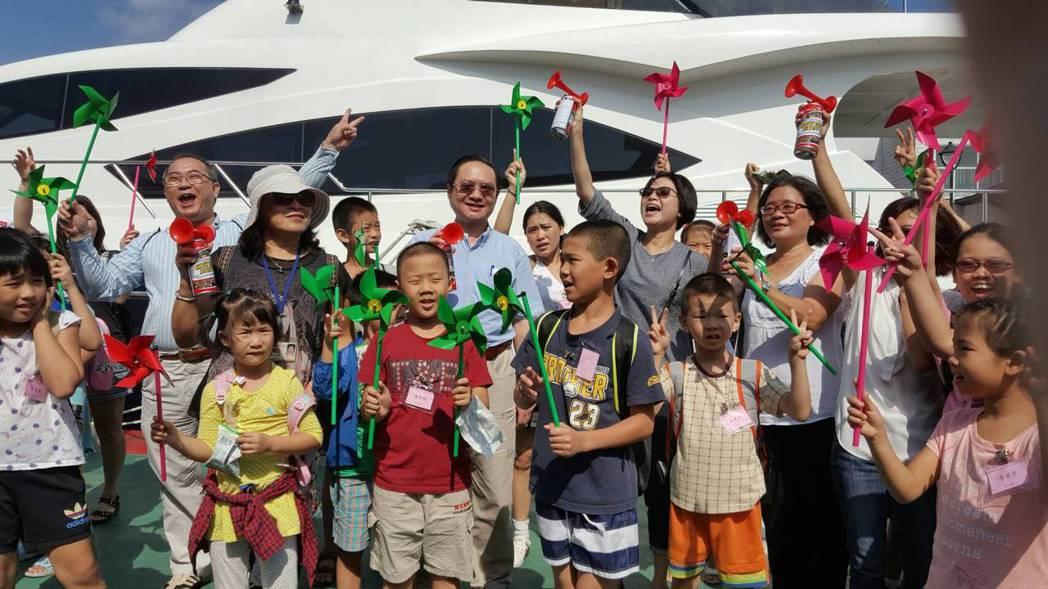 主辦單位發給每位小朋友一支紙風車,小朋友開心合影留念。記者張芮瑜/翻攝