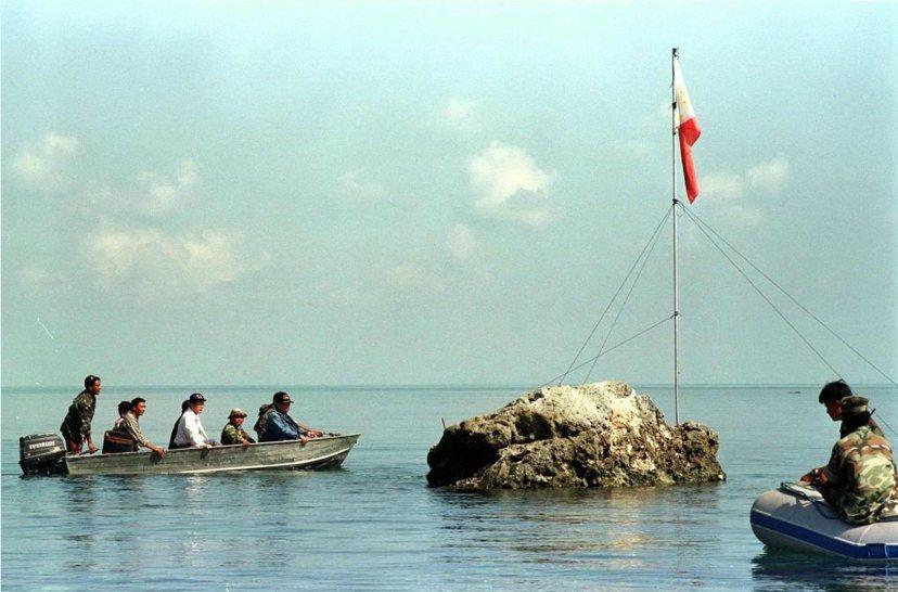1997年菲律賓海軍跟國會議員於黃岩島附近礁岩上插旗幟。 圖/路透社