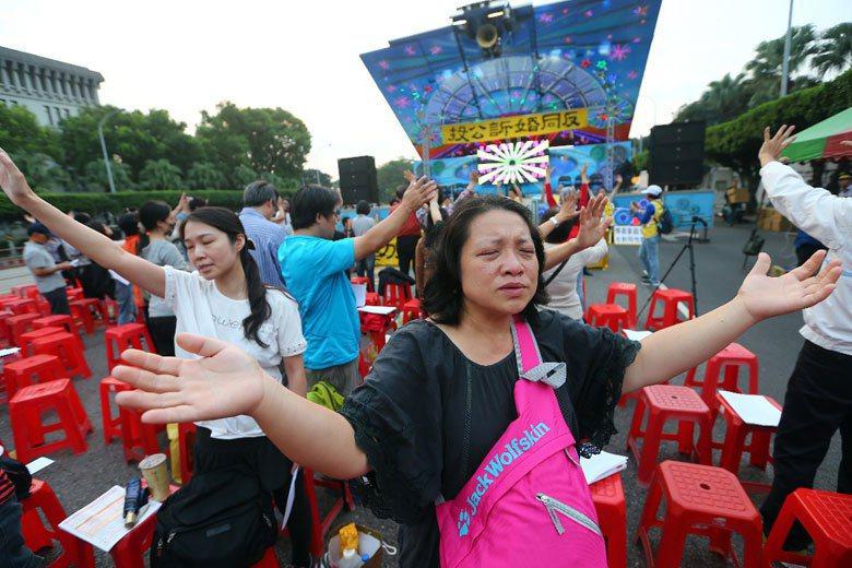 中華世界大同幸福勞動聯盟舉行「反同婚訴公投」記者會,場上民眾閉目唱歌祈福。 攝影/杜建重