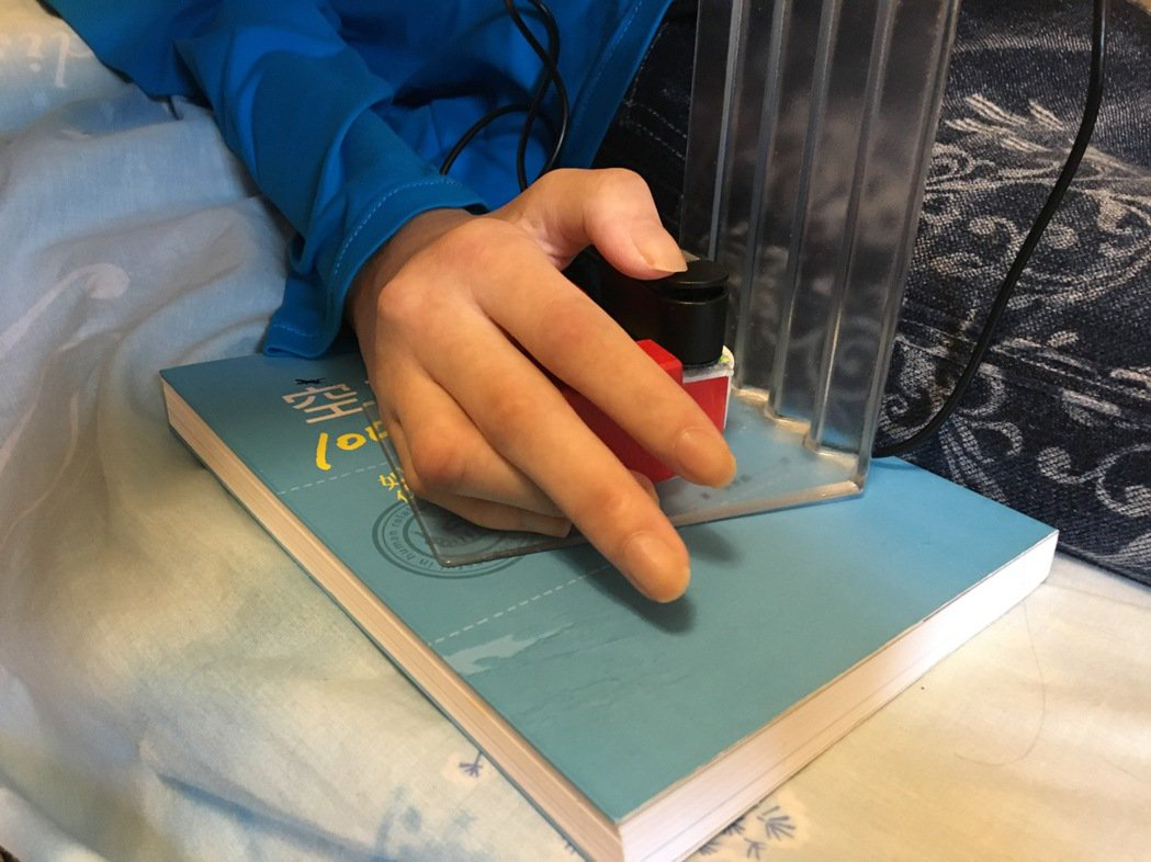 漸凍人「小娟」發病一年全身癱瘓,只能靠手指按壓輕觸鍵,打字在平板內和人溝通。記者...