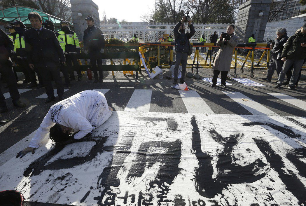 韓國國防部大門外,抗議日韓GSOMIA協定的示威者,正以行動藝術在地上寫下了「反...