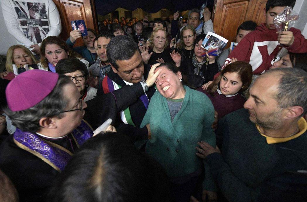 阿根廷的Manuel Acuna主教(左),正在替民眾進行驅魔。 圖/法新社