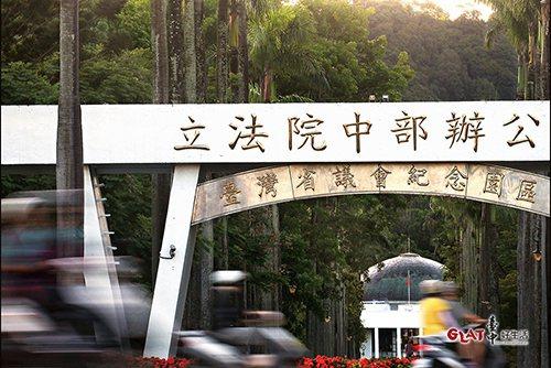 台灣省議會紀念園區入口牌樓新舊並陳,椰林道直通圓頂議事堂。