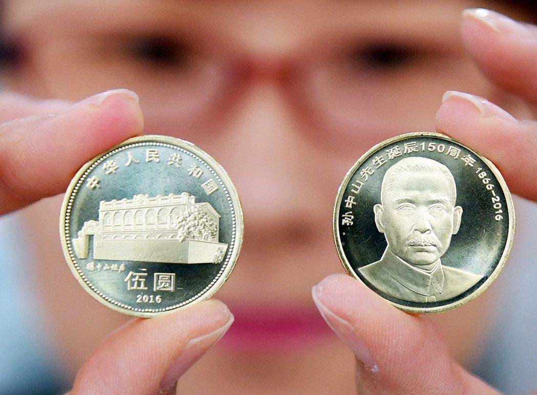 一名工作人員在展示孫中山先生誕辰150週年普通紀念幣的正反面。(新華社)