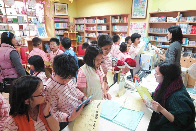 愛心志工協助主題書展閱讀認證。圖片提供/修德國小