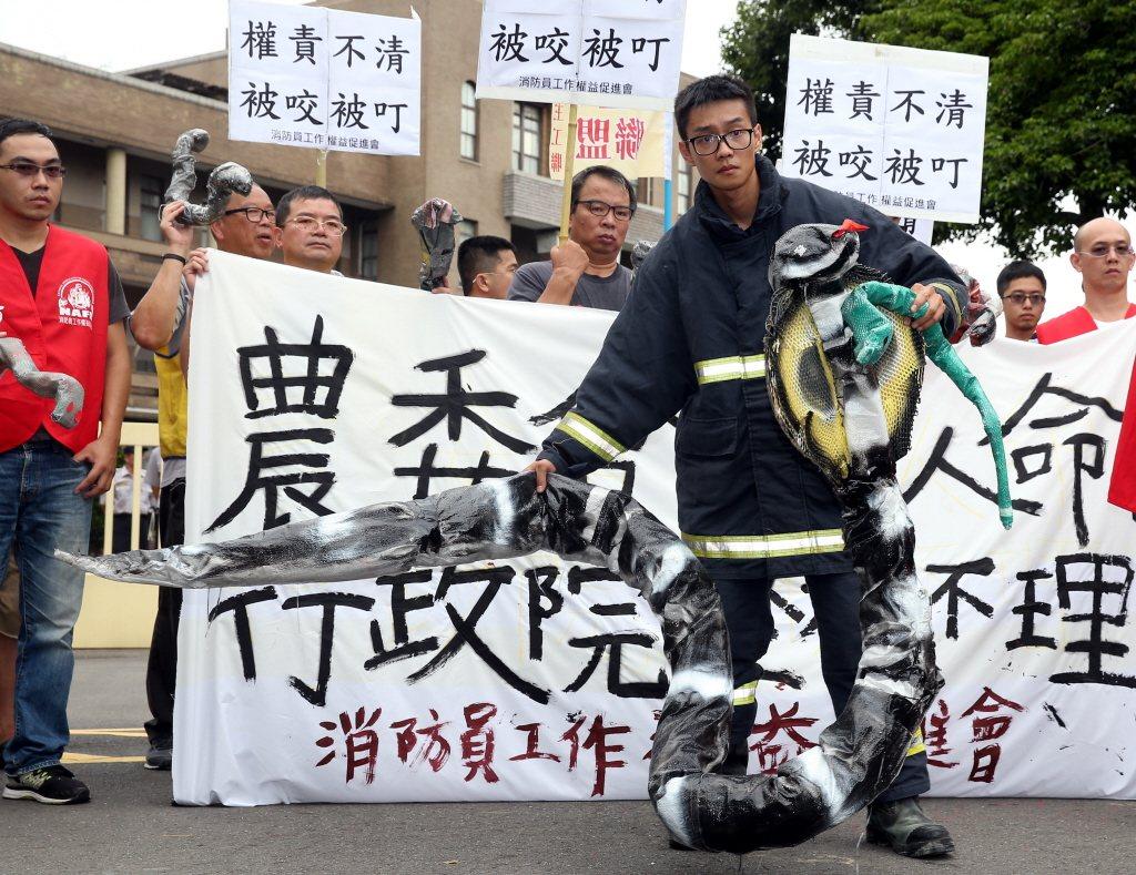 消防員工作權益促進會日前到行政院正門口舉行「捕蜂蛇權責不清 消防員被咬被叮 農委...