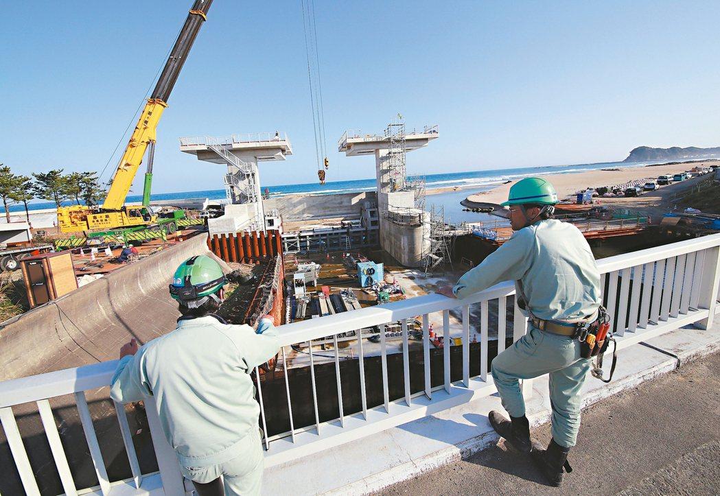 日本福島磐城市的工人上月底在地震引發的海嘯警報解除後,監督水閘門安裝進度。 美聯...