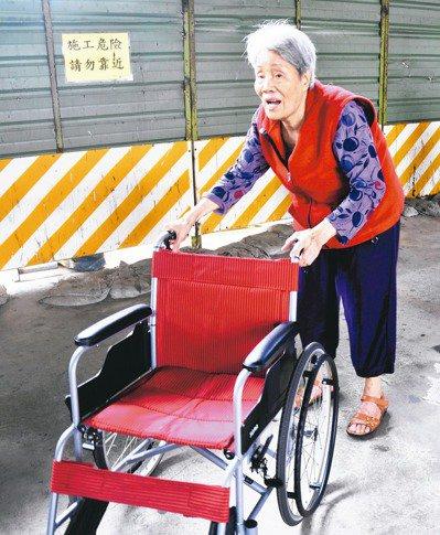 一名阿嬤抓住心愛的輪椅,讓身體動一動。 記者游明煌/攝影