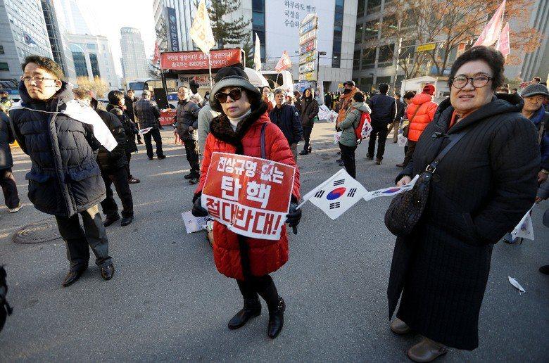 朴槿惠支持者手持「絕對反對彈劾」標語,展現力挺朴槿惠的決心。 圖/美聯社