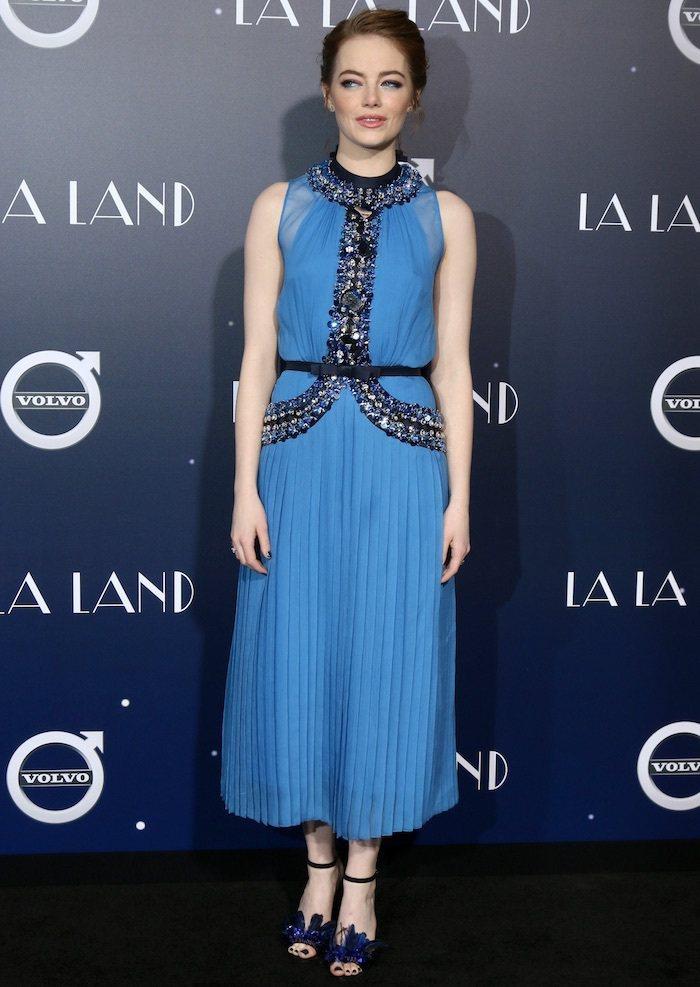 在洛杉磯的首映會中,艾瑪史東穿上Prada的藍色亮片百褶裙禮服搭配Jimmy C...