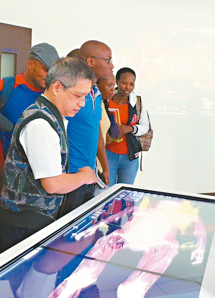 義守大學副教授周明加(左一)為學士後醫學系外國專班學生,示範操作3D虛擬人體解剖...
