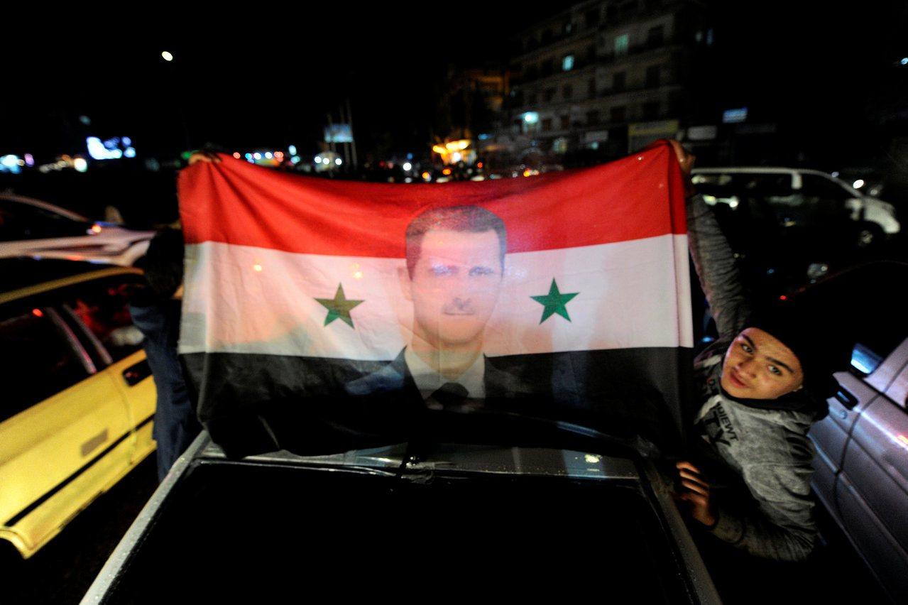 敘利亞內戰停火,民眾在街上展示總統阿塞德及國旗。圖/路透