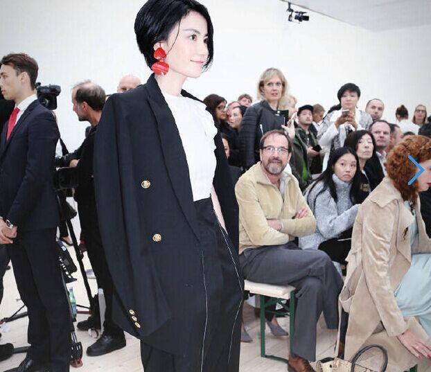 王菲在巴黎時裝周的造型,黑白西裝的簡約風格,右耳單側兩片碩大的紅色耳環,乍看搶眼...