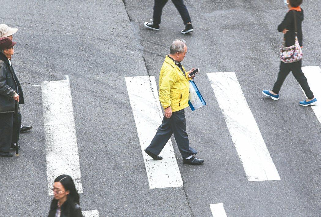 行人過馬路時,一面走路、一面低頭滑手機,已成不少路口常見景象。 記者楊萬雲/攝影