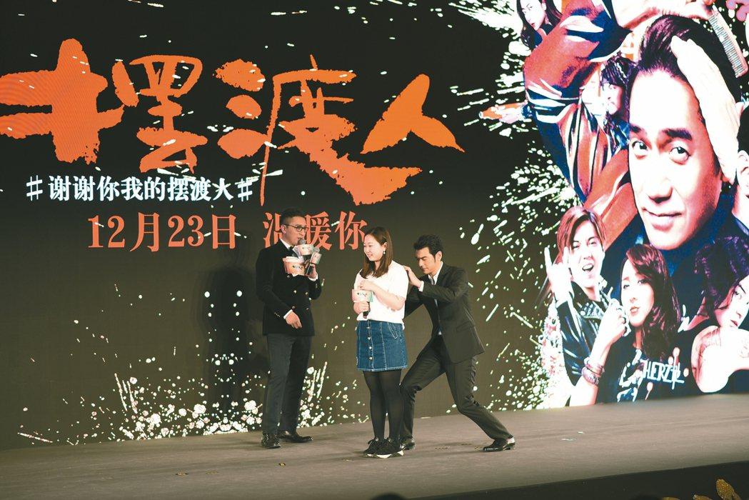 金城武(右)為粉絲簽名,姿勢被虧像岳飛的母親在刺字。 圖/魯皓平攝影、提供