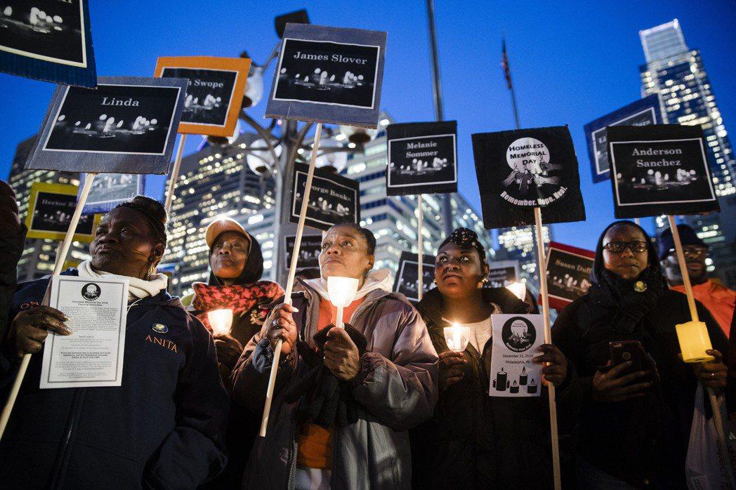 聚集在費城市政大樓外廣場的民眾,在街友紀念日這天守夜致意。手持的標語牌上還有那些...