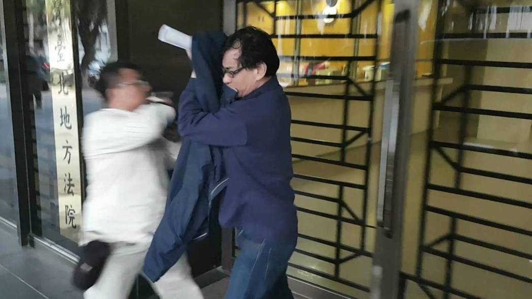 楊肇忠(右)交保後,用衣服擋住臉快速走出地檢署。記者張宏業/攝影