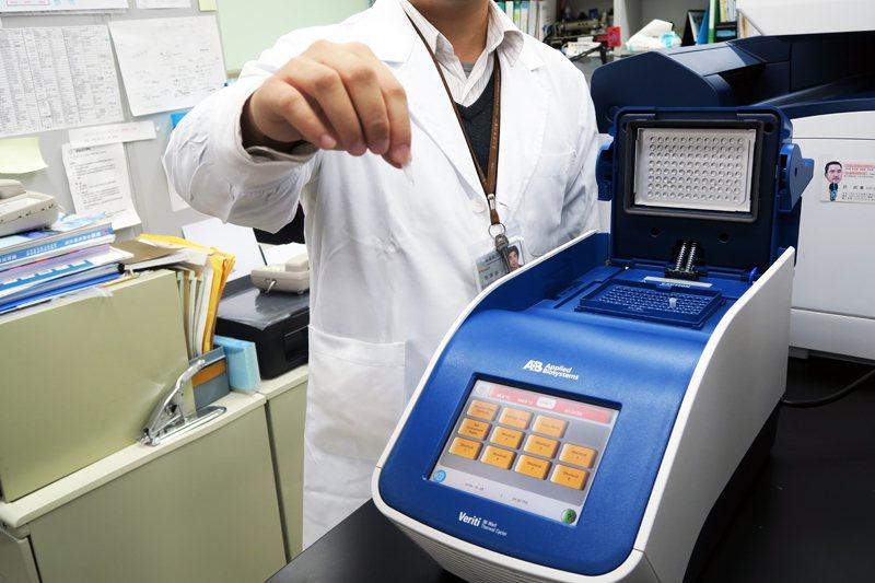 醫事檢驗師操作基因檢測儀器中的「核酸增幅放大反應系統」。(photo by 林亭...