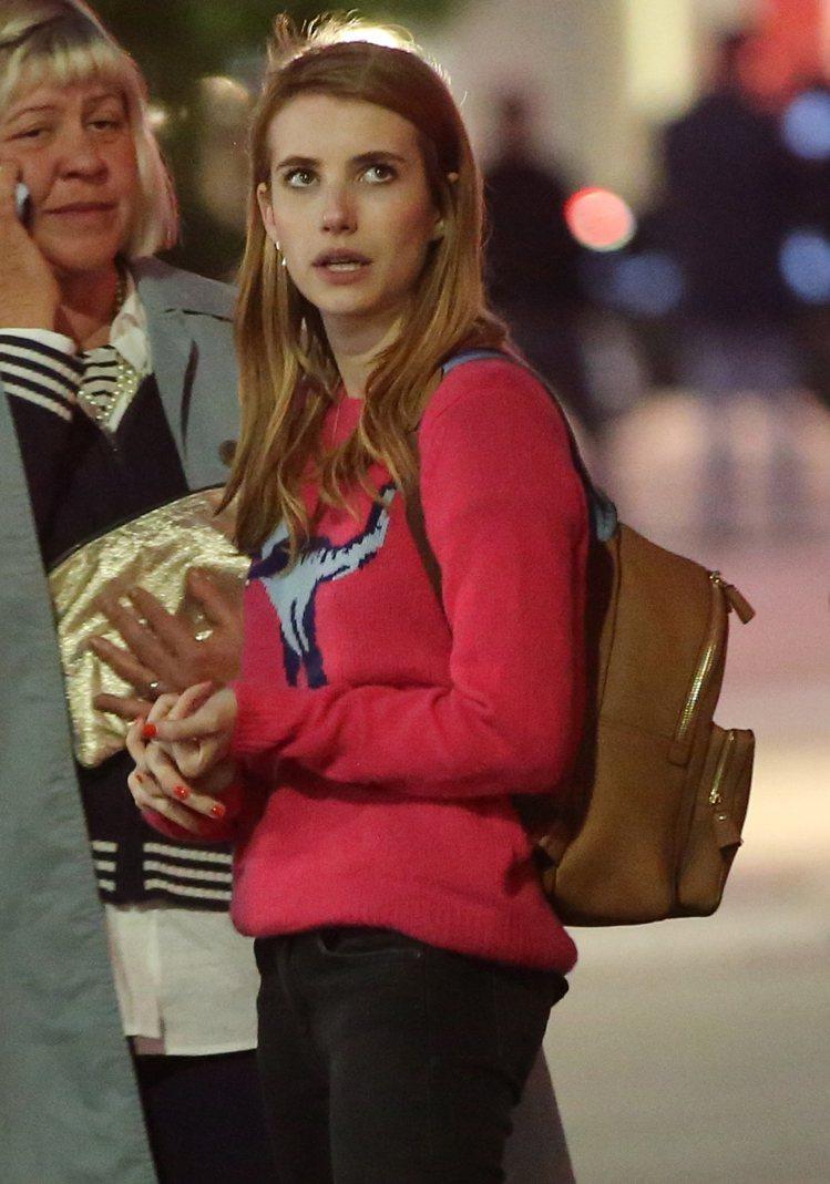 艾瑪羅勃茲身穿桃紅色的Rexy毛衣,顏色相當討喜。圖/COACH提供