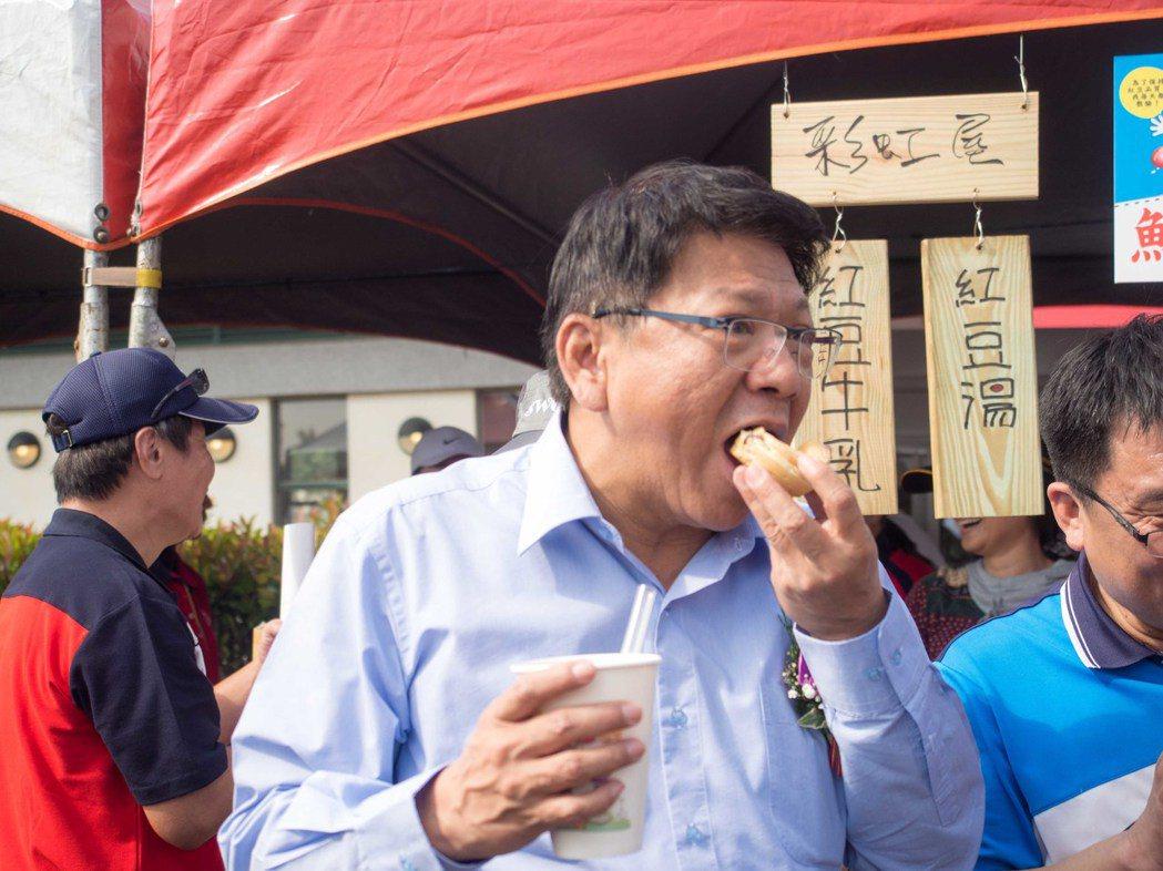屏東縣長潘孟安參與「紅豆牛奶節」時一邊吃著紅豆餅、一邊喝著紅豆牛奶。記者林良齊/...