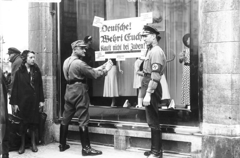 圖中的標語上寫著:「德國人!保衛自己!拒絕購買猶太人的商品」(Deutsche,...