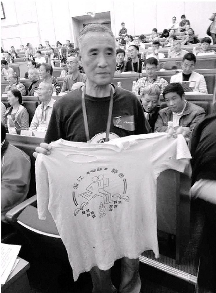 曾啟順展示他參加首屆杭馬時穿過的參賽服,一直珍藏了30年。(取材自錢江晚報)