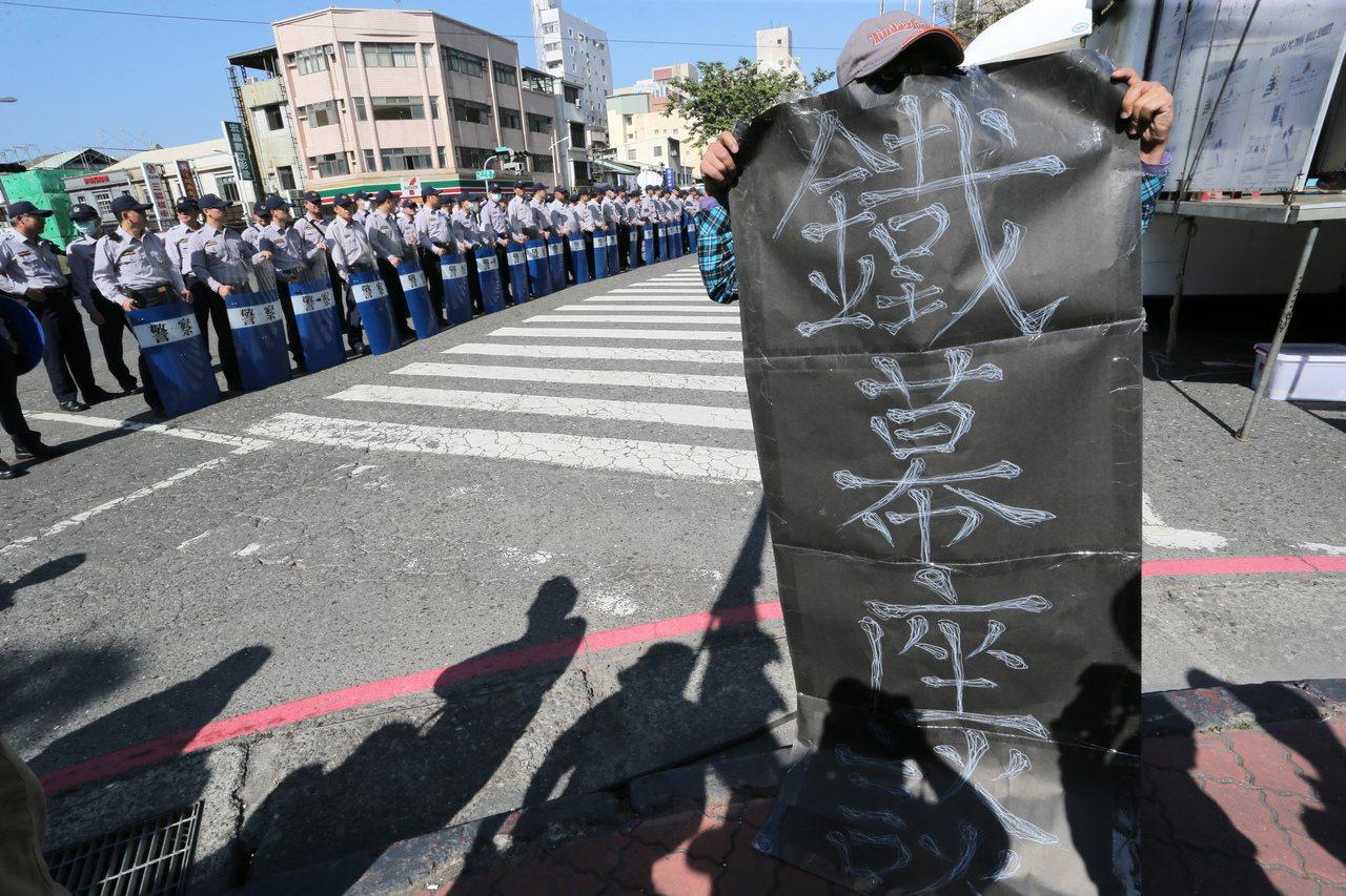 國家年金改革座談會南部場今天登場,反對年金改革的民眾身穿布條,在警方人牆外不滿抗...