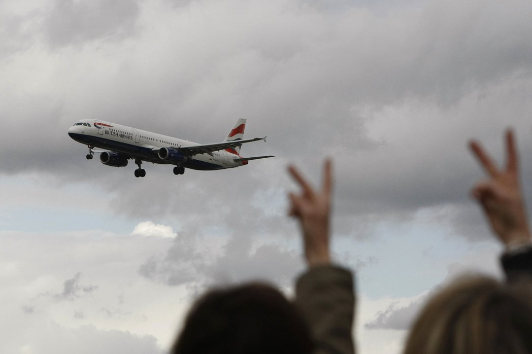 資料圖片:2010年英航大罷工,工會成員朝班機比出挑釁的英式V字手勢。 圖/法新...
