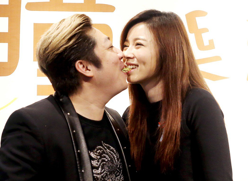 王瞳(右)自創品牌在網路賣台灣在地健康零嘴,艾成(左)到場與王瞳同吃一根長條形方...
