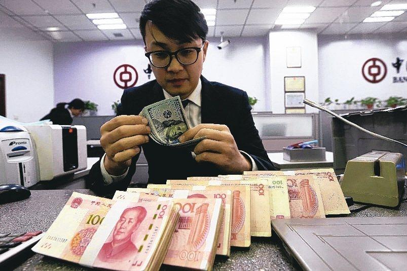 大陸12月新貸款超預期,專家分析經濟不悲觀。圖為銀行行員清點美元和人民幣。 中新...