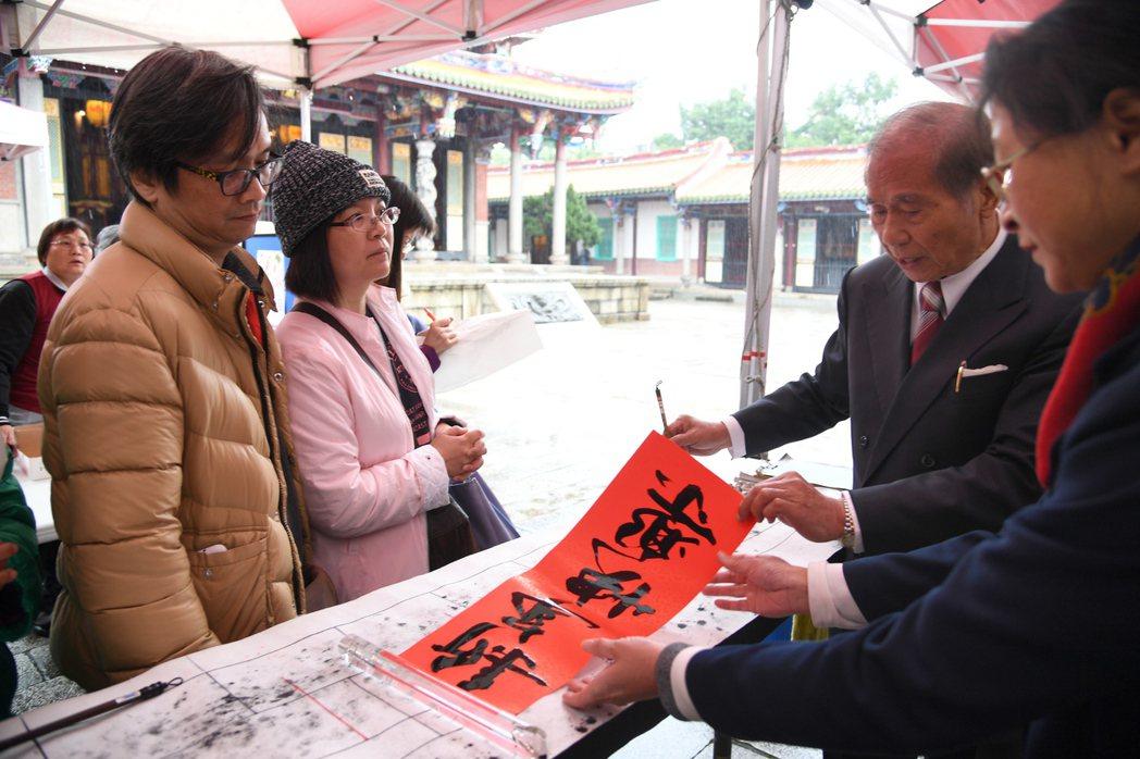 台北孔廟14日舉辦新春揮毫活動,書法名家現場揮毫為民眾寫春聯。 中央社