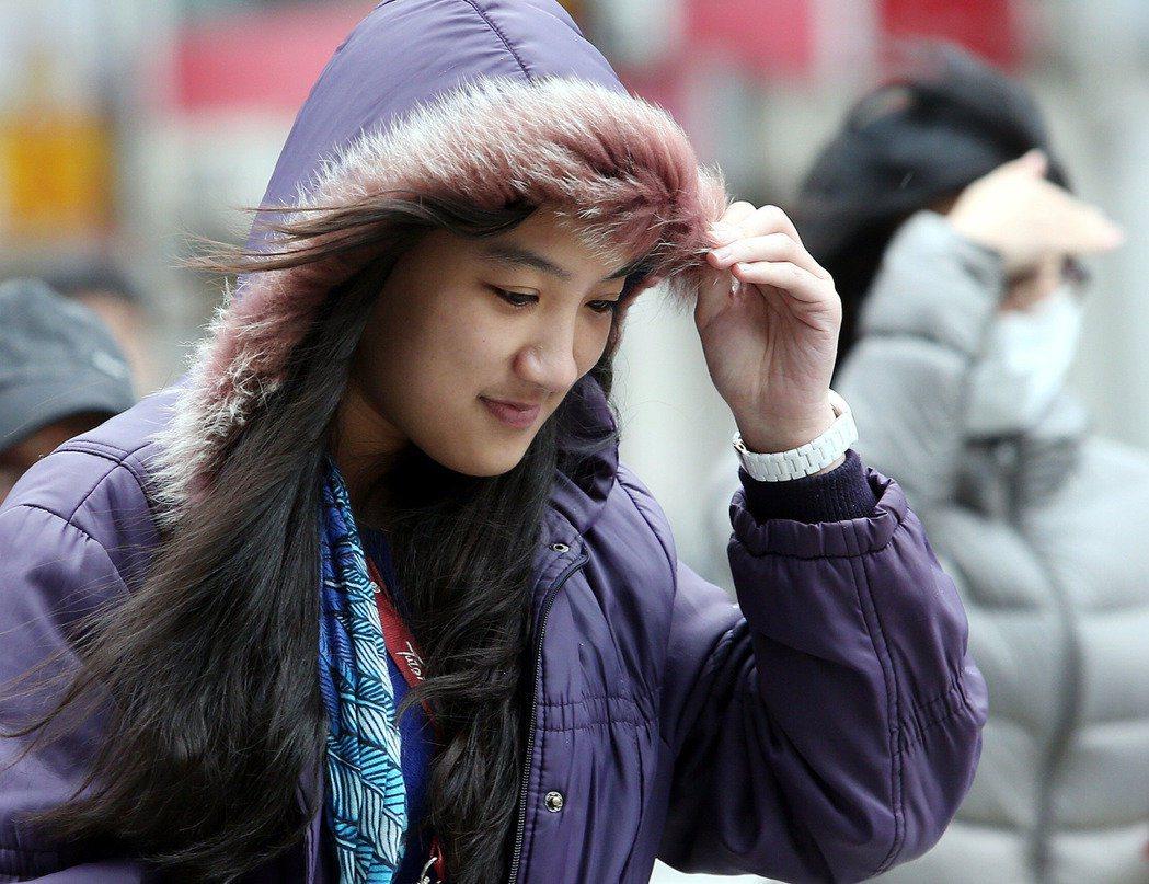 天氣冷颼颼,台北街頭的路上行人,面對陣陣寒風的吹襲,緊抓著連身帽禦寒。本報系資料...