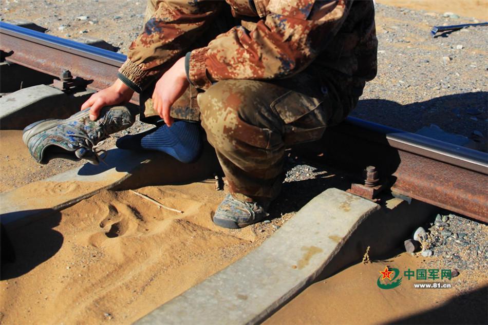 士兵正在清理鞋裡的沙子。(中國軍網)
