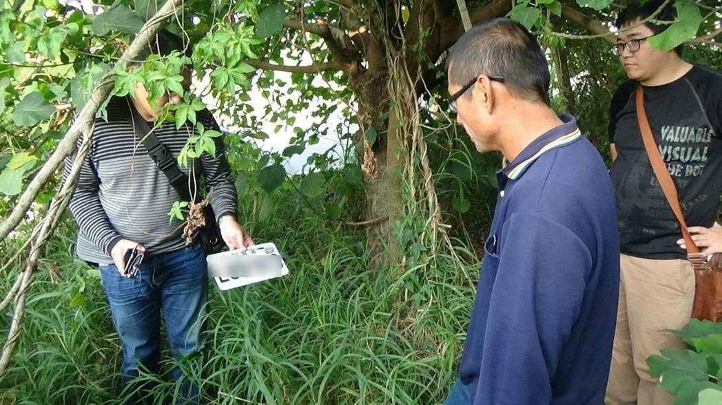 曾姓男子(右二)涉搶被捕,帶警方在草叢內找到他涉案後丟棄的機車贓牌。記者林保光/...