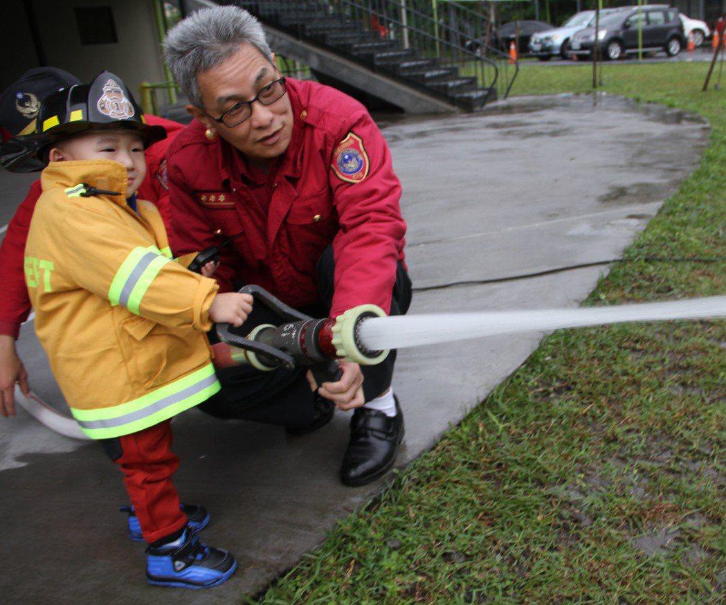 才兩歲的黃小弟弟今天全副武裝,當起打火兄弟,操作錨子射水。記者羅建旺/攝影