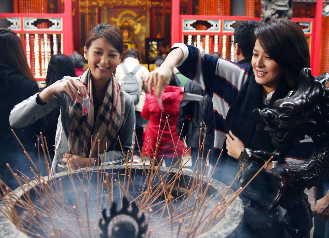 蘇晏霈(右)、樓心潼(左)到龍山寺拜拜求桃花緣份,拿到紅線後過爐火。記者杜建重/...