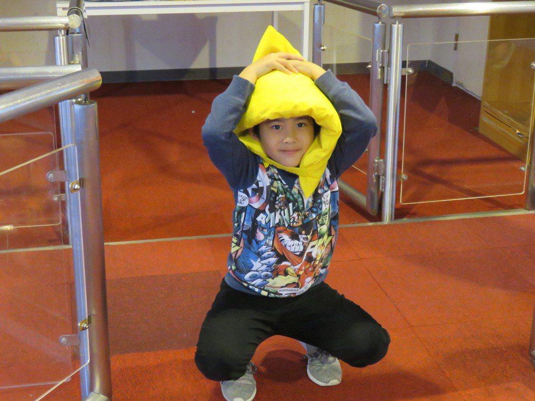 學童在北市防災教育館戴防災頭套體驗地震模擬。記者雷光涵/攝影