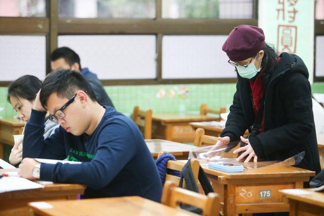 106學年大學學科能力測驗今天登場,一名媽媽考前替應考的兒子整理桌面,幫他鋪上軟...
