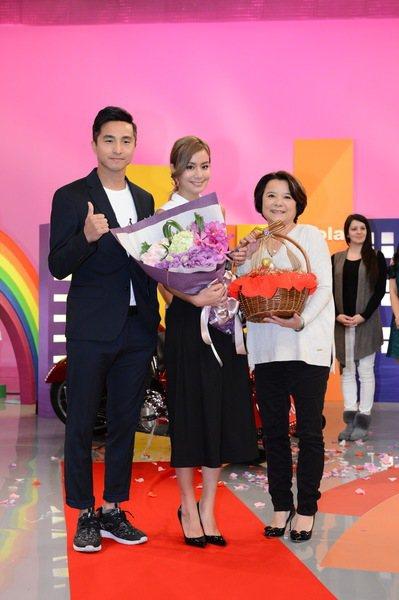 王少偉(左)、莎媽(右)22日在八大電視台棚內獻花並送上金雞籃,祝賀莎莎(中)首