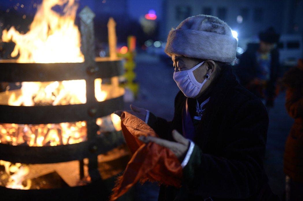 祭火儀式:一名內蒙古長輩手持哈達祈福。 圖/中新社