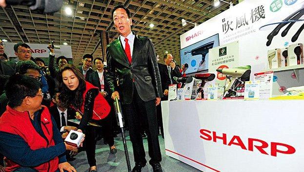 不只賣大電視,為推銷夏普產品,郭董(中)在尾牙現場當起銷售員,親自試用吸塵器。(...