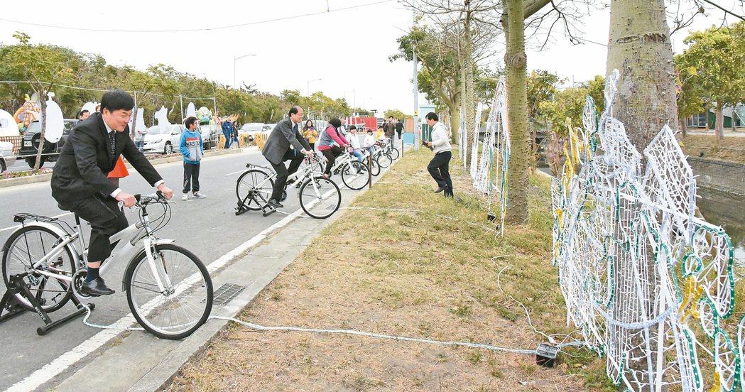 北港鎮長張勝智(左)和虎尾鎮長林文彬(左二)踩單車發電點燈。 記者蔡維斌/攝影
