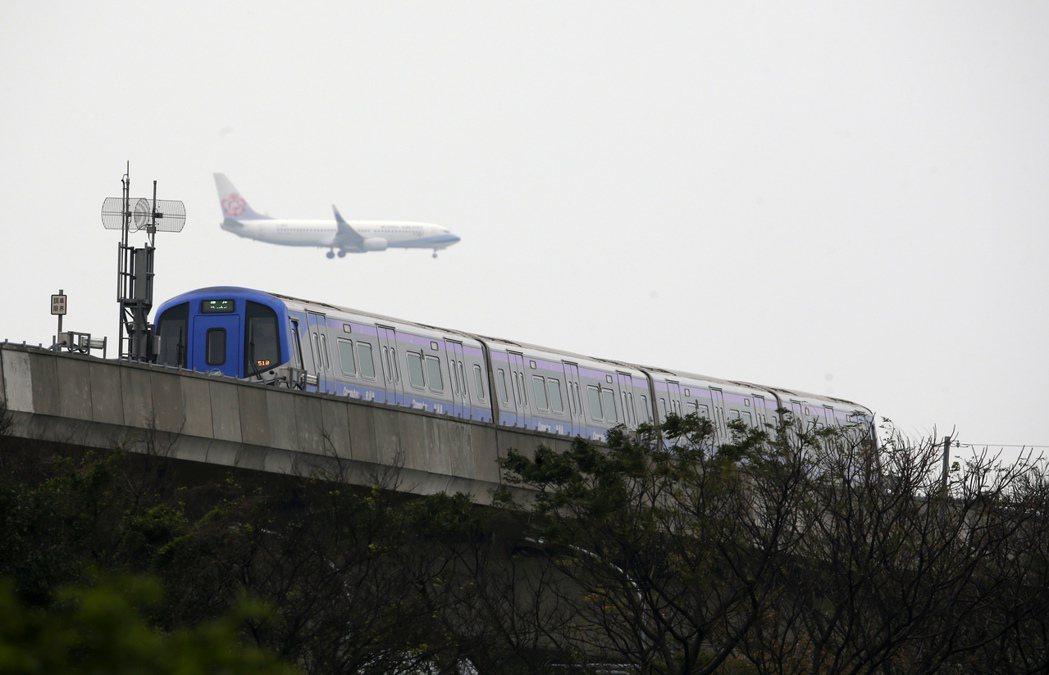 等了20年,機場捷運終於開出第一班車,在桃園機場附近,可以看見飛機與捷運同時在桃...