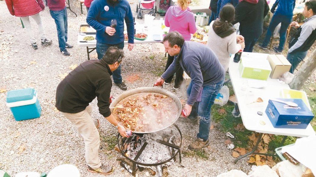 海鮮飯完成後,通常會由兩位男士合力把海鮮飯鍋扛下爐火。 攝影/周育如
