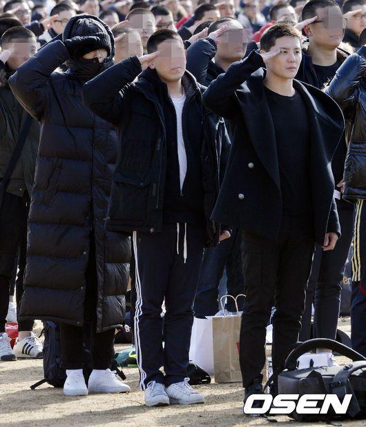 金俊秀(右)和T.O.P(後方戴毛帽者)舉手敬禮。圖/摘自OSEN