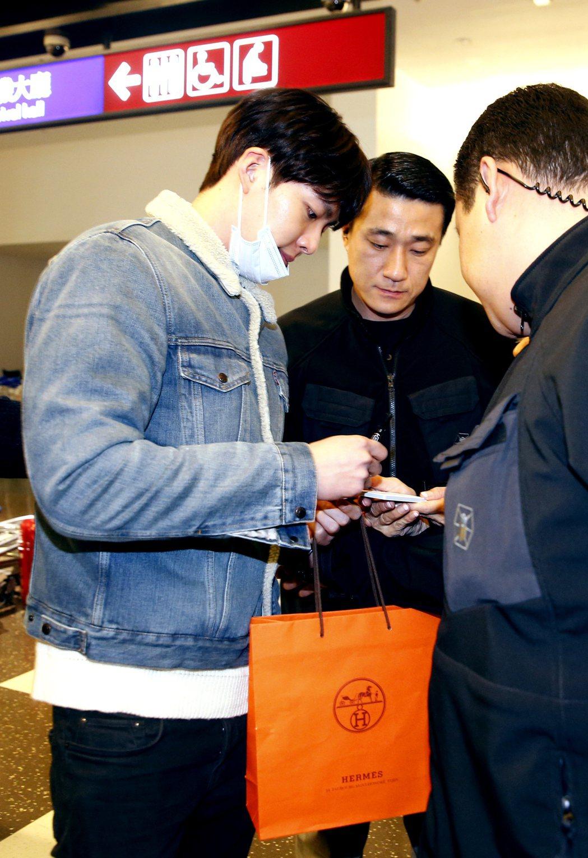 韓星金宇彬晚上搭乘KE-693班機抵達桃園機場,一位幸運的粉絲獲得簽名。記者鄭超...